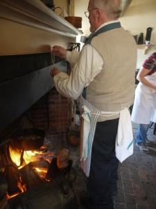 John Hammond hangs the chicken over the fire.