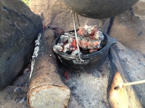 cooking biscuits in an dutch oven using hot coals under and on top.