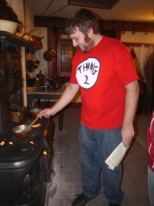 Frederick Adlhoch stirs the custard sauce for tarts over the woodstove.