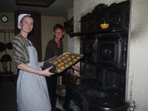 Interpretive instructor puts Orange Gingerbread cookies into the oven while Nancy Di Federico watches on.