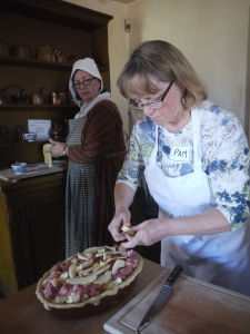 Pam Edmonds adds ingredients to a Pork Pie as volunteer Sherry Murphy looks on.