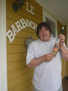 Leonce Arsenault holds a bottle of Bagosse in front of his shop.