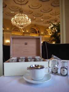 The Tea Box and a simple elegant tea service against a lobby dripping with history