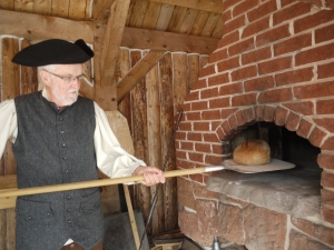 George Doughart puts a loaf of Soldier style bread into the Roma brick bread oven