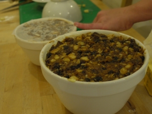 Patting the mixture for the Christmas Pudding into bowls for steaming.