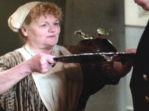 Mrs. Patmore proudly carries a dessert to the serving staff