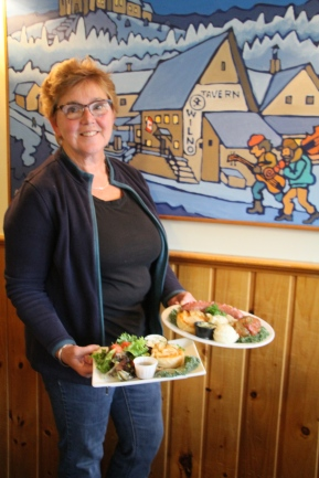 Corinne Higgins serves two special plates of Polish food against a backdrop of a painting of Wilno by Linda Sorensen